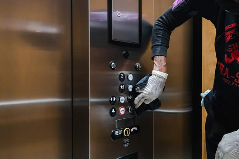 worker impliments touch-point cleaning on an elevator